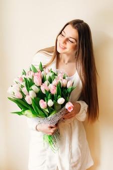 Счастливая девушка с длинными волосами большой букет из белых и розовых тюльпанов.