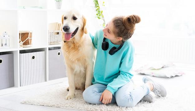 明るい部屋で素敵なゴールデンレトリバー犬と幸せな女の子