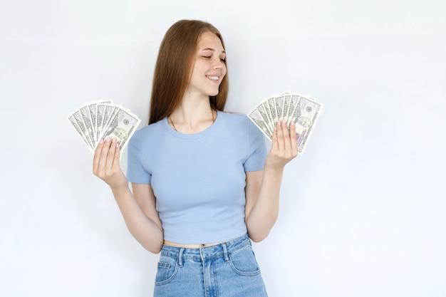 灰色の背景に青いtシャツでお金と幸せな女の子
