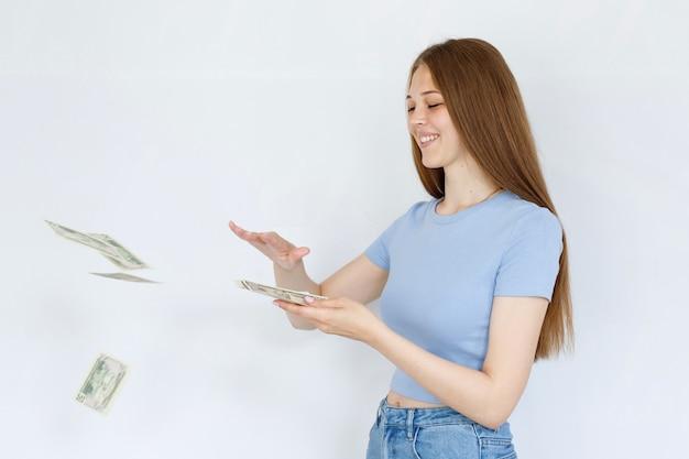 灰色の背景にお金と幸せな女の子