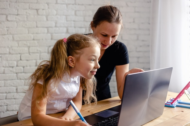 家でオンライン勉強している母親と幸せな女の子。コロナウイルスと検疫の概念。オンライン学習または教育技術の概念