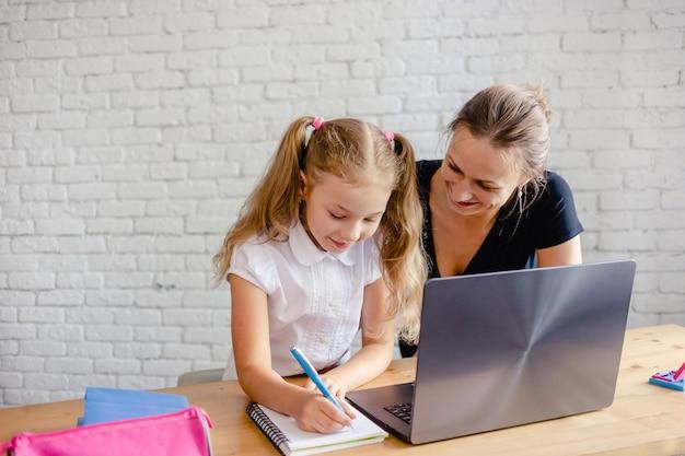 Счастливая девушка с матерью, обучающейся онлайн дома. концепция технологии онлайн-обучения или образования