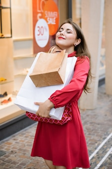 Happy girl with paper bags while shopping goods. concept of sale season