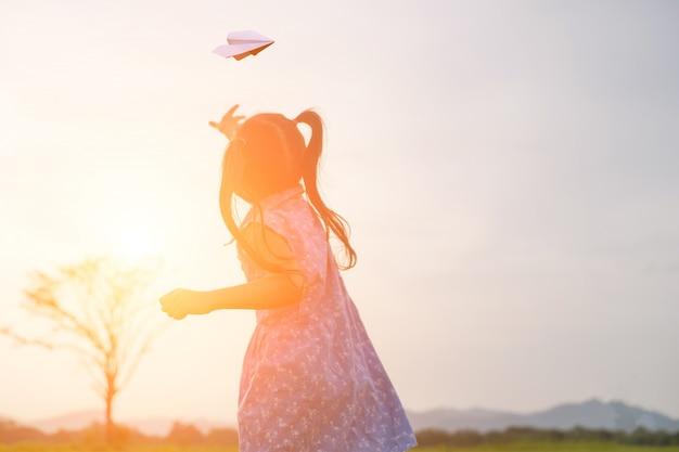 彼女の手で紙飛行機で幸せな女の子。