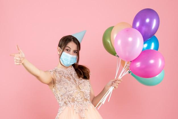 ピンクのカラフルな風船を保持しているパーティーキャップと医療マスクを持つ幸せな女の子