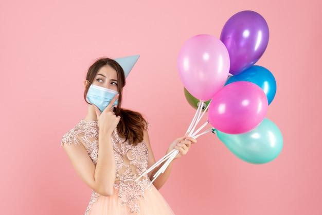 ピンクの彼女のあごに手を置くカラフルな風船を保持しているパーティーキャップと医療マスクを持つ幸せな女の子