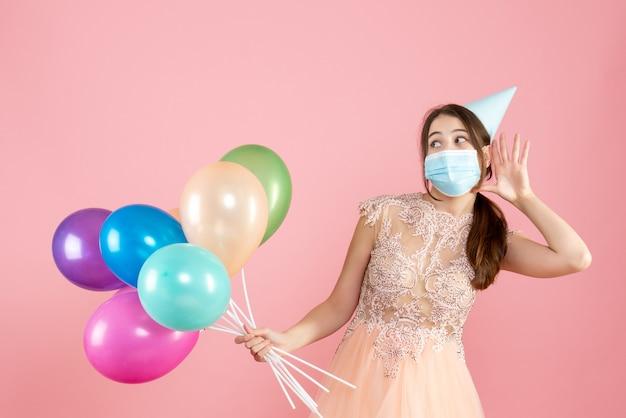 ピンクのカラフルな風船を保持しながら何かを聞いているパーティーキャップと医療マスクを持つ幸せな女の子