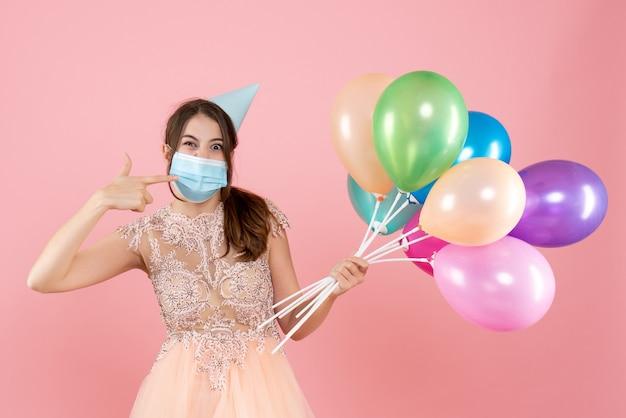 ピンクのカラフルな風船を保持している彼女のマスクを指しているパーティーキャップと医療マスクを持つ幸せな女の子