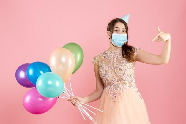 ピンクのカラフルな風船を持って自分を指しているパーティーキャップと医療マスクを持つ幸せな女の子