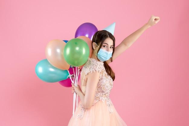 ピンクの彼女の背中の後ろにカラフルな風船を保持しているスーパーヒーローのポーズで立っているパーティーキャップと医療マスクを持つ幸せな女の子