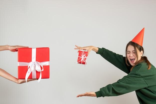 Ragazza felice con il tappo del partito confrontando il suo regalo con il dono della holding della mano umana su bianco