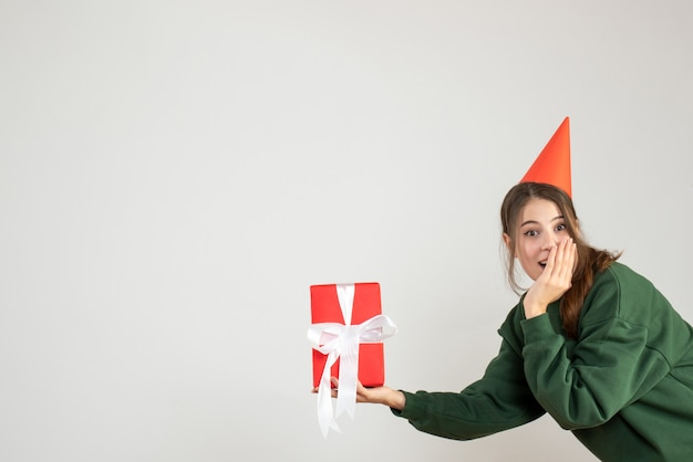 화이트 크리스마스 선물을 들고 파티 모자와 함께 행복 한 소녀