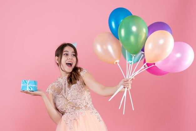 핑크에 다채로운 풍선과 선물을 들고 파티 모자와 함께 행복 한 소녀