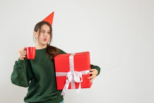 흰색에 그녀의 크리스마스 선물과 컵을 들고 파티 모자와 함께 행복 한 소녀