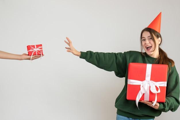 Ragazza felice con la protezione del partito che tiene il suo regalo di natale e regalo della holding della mano umana su bianco