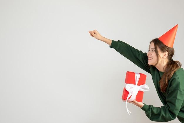 Счастливая девушка в кепке в позе супергероя держит подарок на белом