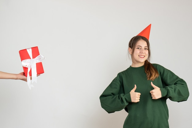 Happy girl with party cap making thumb up sign and human hand holding gift on white