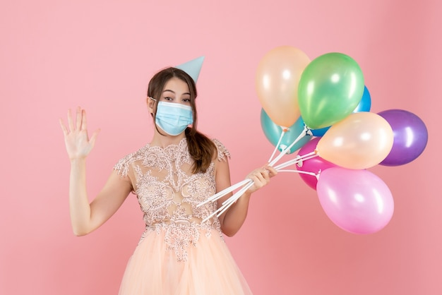 Happy girl with party cap and medical mask say hello holding colorful balloons on pink
