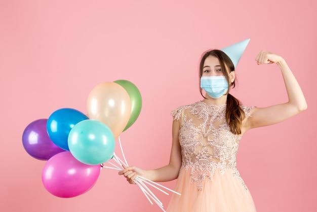 Ragazza felice con cappello da festa e mascherina medica che mostra i muscoli che tengono palloncini colorati sul rosa