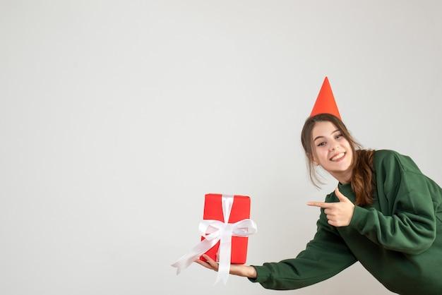 Ragazza felice con il tappo del partito che punta al regalo su bianco