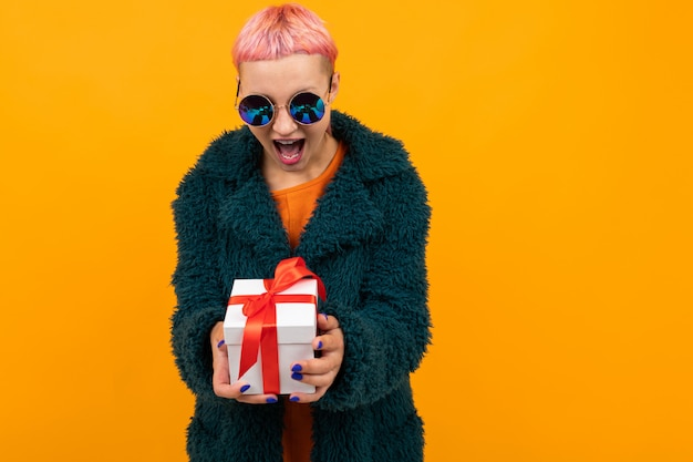 Happy girl with pink hair with a nose and tongue piercing dressed in a fur coat and glasses holds a gift on yellow