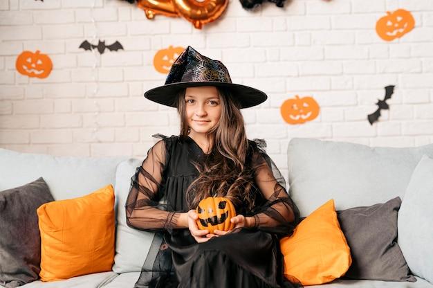 Счастливая девушка с тыквой на диване дома концепция праздника хэллоуина и октября детство