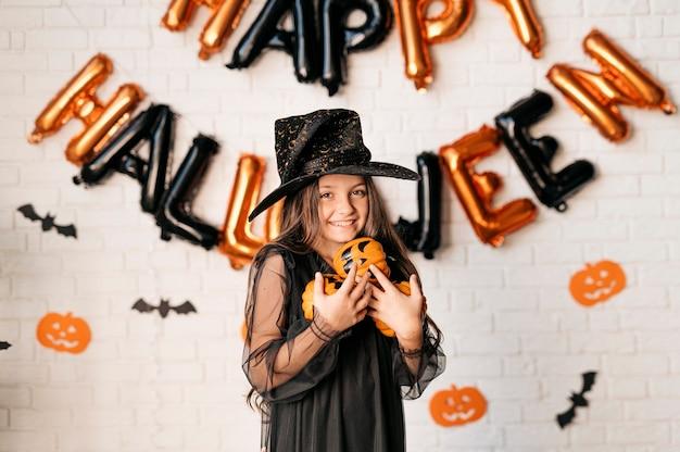 Счастливая девушка с тыквами в руках на фоне стены, украшенной воздушными шарами хэллоуина