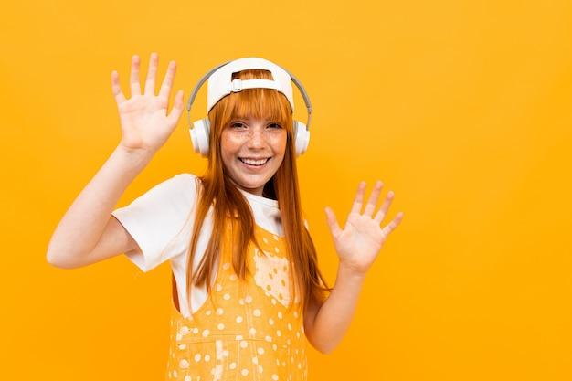 赤い髪の幸せな女の子は大きな白いイヤホンで音楽を聴き、黄色の背景に分離された笑顔