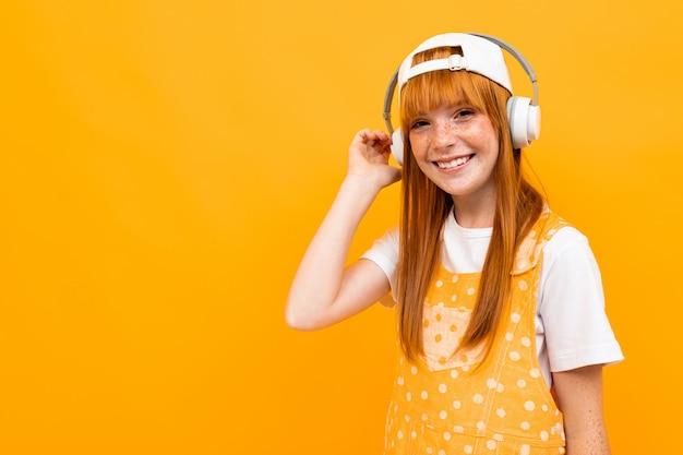 赤い髪の幸せな女の子は大きな白いイヤホンで音楽を聴くし、黄色に分離された笑顔