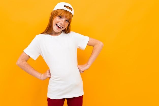 赤い髪の笑顔と黄色の背景に分離されたgesticulatesと幸せな女の子