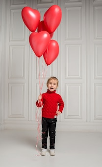 Happy girl with red heart shaped balloons on white