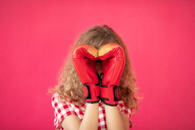 Счастливая девушка с красными боксерскими перчатками в форме сердца на розовом фоне концепция дня святого валентина