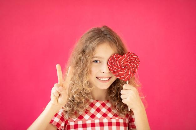 Счастливая девушка с красным леденцом на палочке в форме сердца на розовом фоне концепции дня святого валентина