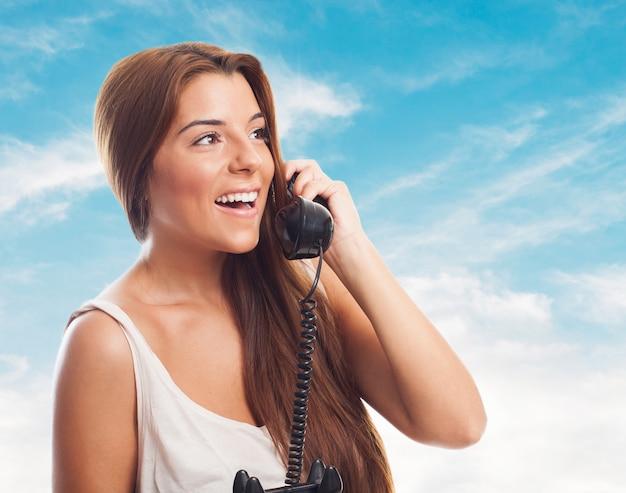Счастливая девушка с ротационным телефон говорить через трубку