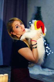 クリスマスの装飾でサモエドハスキー犬と幸せな女の子