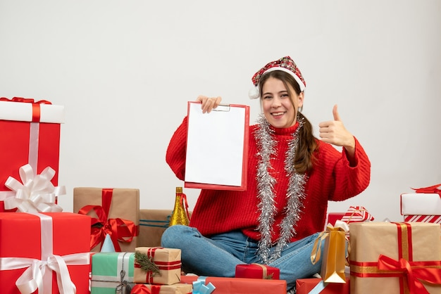 Happy girl with santa hat holding files making thumb up sign sitting around presents on white