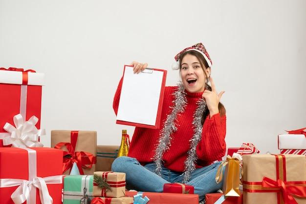 白のプレゼントの周りに座っているファイルを保持しているサンタの帽子と幸せな女の子