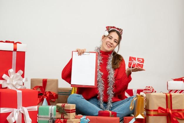 산타 모자 지주 선물 및 문서 주위에 앉아 행복 소녀 흰색 선물