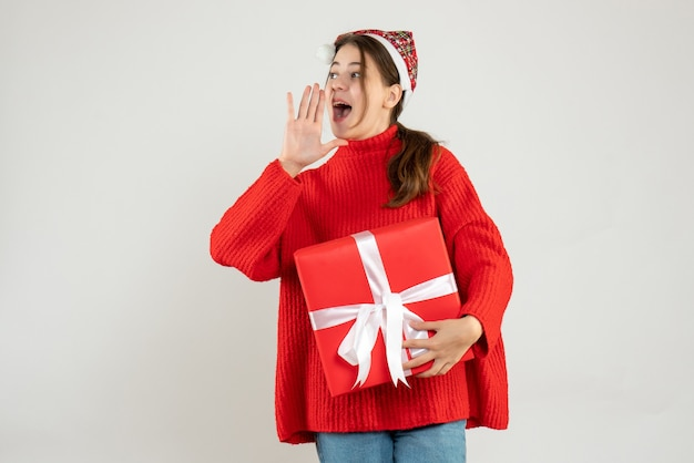 Happy girl with santa hat holding gift calling someone on white