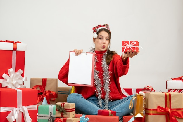 Happy girl with santa hat holding gift and document sitting around presents on white