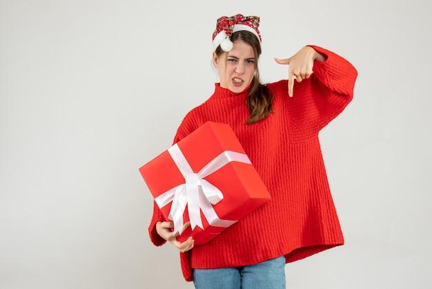 Счастливая девушка в шляпе санта-клауса держит подарок пальцем, указывая вниз на белом