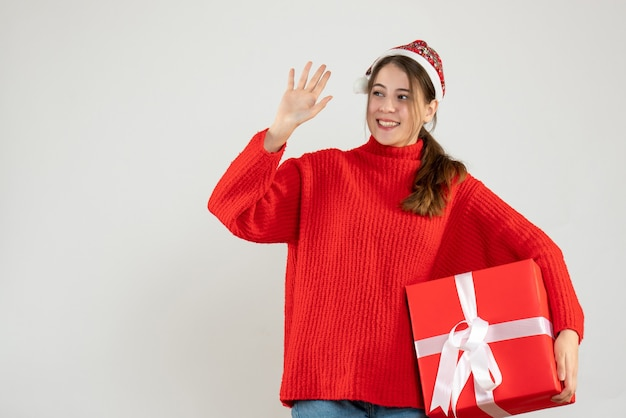 Happy girl with santa hat holding gift and hailing someone on white