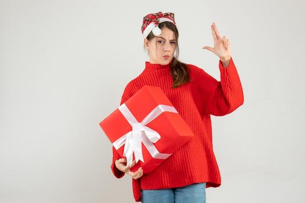 화이트에 손가락 총을 만드는 선물을 들고 산타 모자와 함께 행복 한 소녀