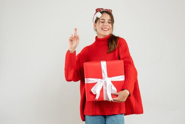 화이트에 행운을 빌어 요 기호를 만드는 선물을 들고 산타 모자와 함께 행복 한 소녀