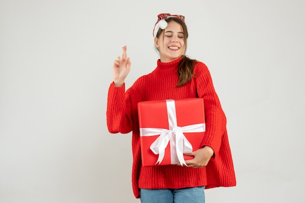 Happy girl with santa hat holding gift making good luck sign on white