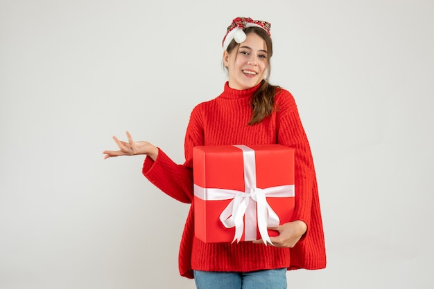 Happy girl with santa hat holding gift on white
