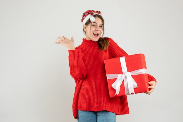 Happy girl with santa hat holding giftbox standing on white