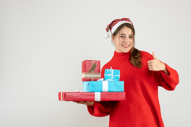 Happy girl with santa hat holding her xmas gift making thumb up gesture on white