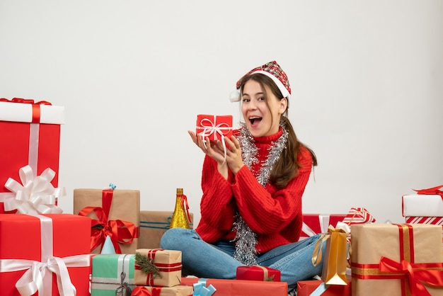 흰색 선물 주위에 앉아 양손으로 현재 들고 산타 모자와 함께 행복 한 소녀