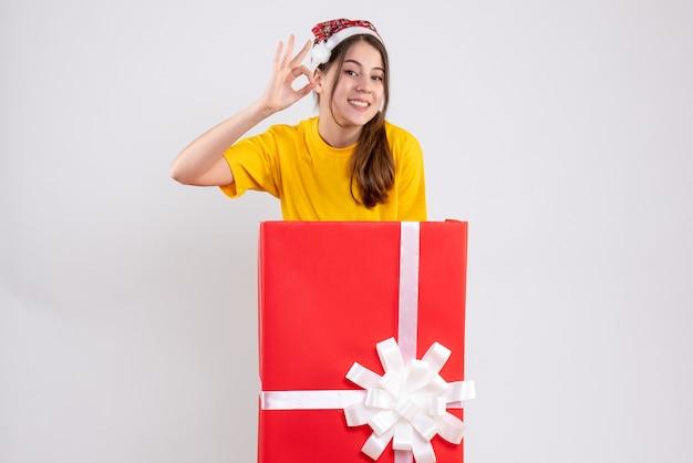 화이트에 큰 크리스마스 선물 뒤에 서 좋아요 기호를 만드는 산타 모자와 함께 행복 한 소녀